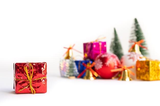 Caixa de presente de natal e árvore com sinos de ouro, pinhas no fundo branco
