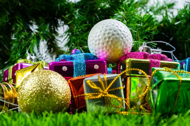 Caixa de presente de natal e bola de golfe na grama
