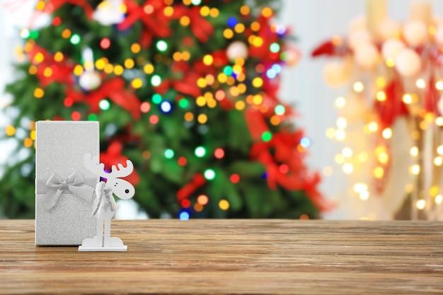 Caixa de presente de natal e cervo decorativo na mesa de madeira