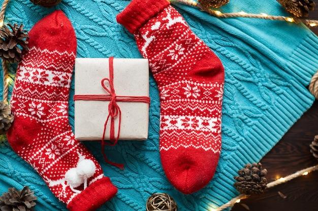 Caixa de presente de natal e meias vermelhas, uma camisola de malha azul e uma grinalda com cones. orientação horizontal