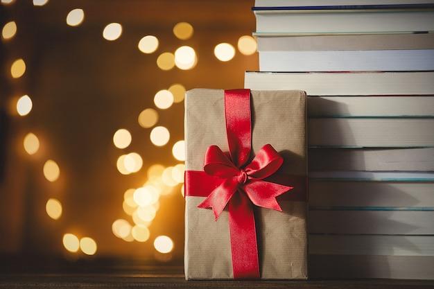 Caixa de presente de natal e pilha de livros com luzes de fada