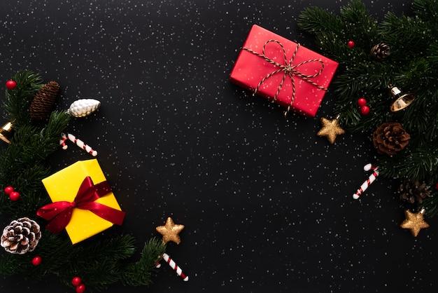 Caixa de presente de natal e pinheiro com decoração de natal em fundo preto