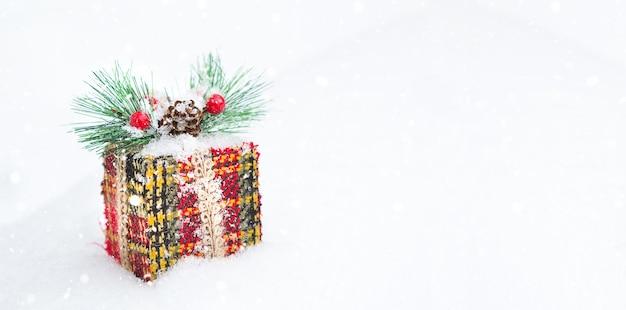 Caixa de presente de natal em um fundo de neve branca com neve e flocos de neve. decorado com ramo de abeto com bagas e cones, envolto numa embalagem quente de malha. ano novo. copie o espaço