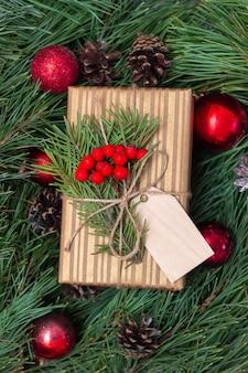 Caixa de presente de natal em um invólucro de artesanato com um galho de uma árvore de abeto em branco para o texto de saudação