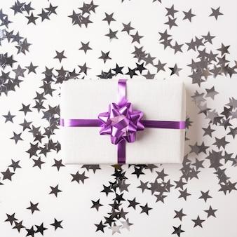 Caixa de presente de natal na mesa branca com estrela de prata