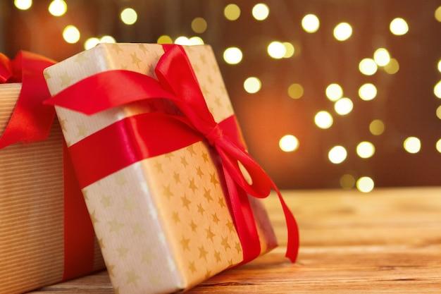 Caixa de presente de natal na mesa de madeira contra o fundo marrom bokeh