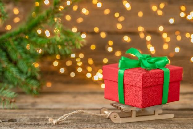 Caixa de presente de natal no trenó com fundo de madeira com luzes desfocadas