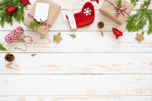 Caixa de presente de natal, pinhas, estrela vermelha e sino em um fundo de madeira.