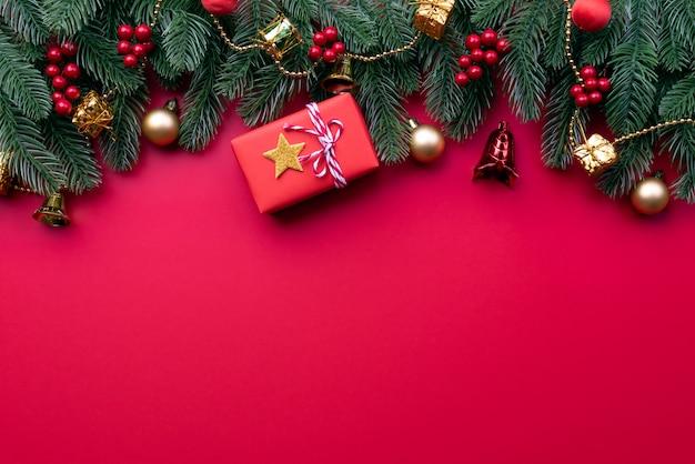 Caixa de presente de natal, ramos de abeto, bagas vermelhas e sino sobre fundo vermelho.