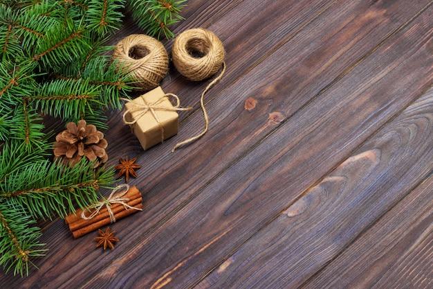 Caixa de presente de natal. ramos de abeto com canela e anis em fundo de madeira rústico. configuração plana. saudações sazonais. conceito de férias de inverno