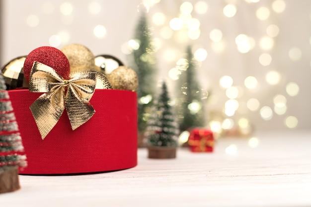 Caixa de presente de natal vermelha com um laço de ouro no fundo do bokeh, árvores de natal e brinquedos.