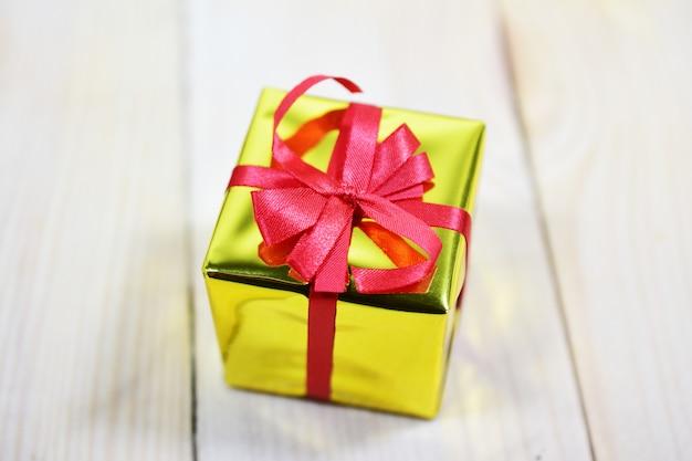 Caixa de presente de ouro na mesa de madeira