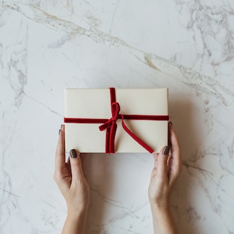 Caixa de presente de papel artesanal em mulheres com as mãos no mármore. conceito mínimo de celebração festiva de natal. camada plana, vista superior.