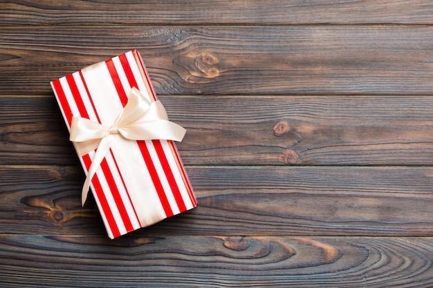 Caixa de presente de papel com fita colorida sobre fundo escuro de madeira. vista superior com espaço de cópia conceito de férias de natal