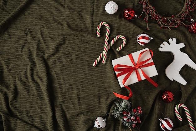 Caixa de presente de papel com gravata borboleta e enfeites de natal, bastões de doces, brinquedos no cobertor verde amassado. vista superior, configuração plana.