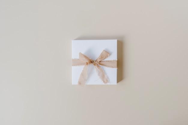 Caixa de presente de papel com gravata borboleta em bege pastel. vista superior, configuração plana. surpresa de feriado de ano novo de natal.