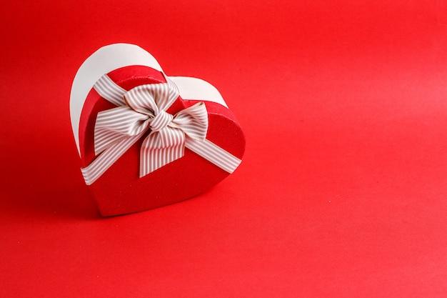 Caixa de presente de papelão biodegradável em forma de um coração com fitas em vermelho
