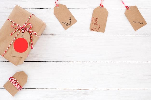 Caixa de presente de presente de natal com etiquetas no fundo de madeira branca. desenho plano criativo, design de vista superior.