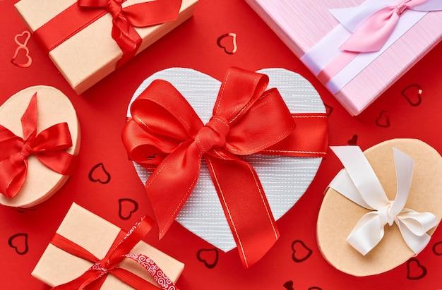 Caixa de presente de várias opções em forma de coração com uma fita vermelha sobre um fundo vermelho. cartão postal do conceito de dia dos namorados. vista do topo.