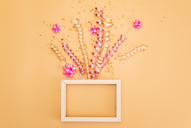Caixa de presente de yelow com vários confetes do partido, flâmulas, noisemakers e decoração em um fundo alaranjado.