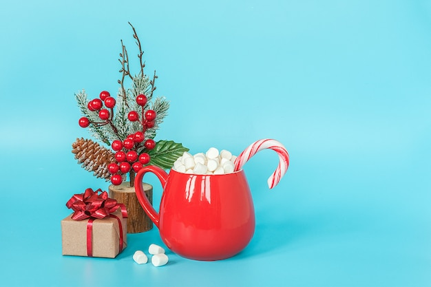 Caixa de presente, decoração de natal e copo vermelho de marshmallows com pirulito na parede azul.