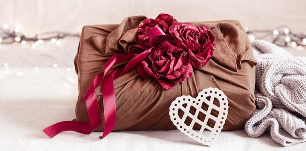 Caixa de presente decorada com fitas e rosas decorativas em peças de malha. embalagem de presente original para o dia dos namorados.
