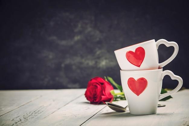 Caixa de presente do dia dos namorados copos vermelhos e rosas em um fundo de madeira.