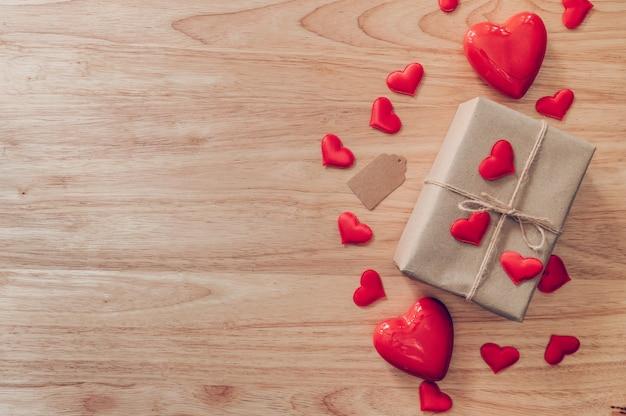 Caixa de presente do marrom da vista superior e coração vermelho no fundo de madeira para o dia dos namorados com espaço da cópia.