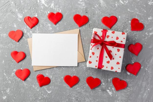 Caixa de presente dos namorados, corações vermelhos, cartão em branco e envelope do ofício