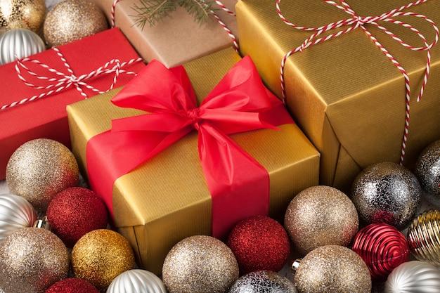 Caixa de presente dourada amarrada com uma fita vermelha.
