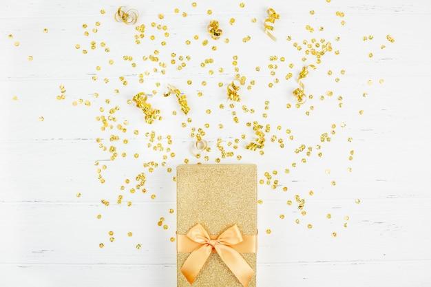 Caixa de presente dourada com confete