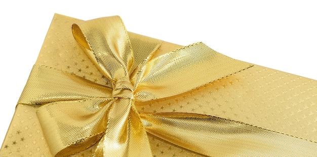 Caixa de presente dourada com fita dourada isolada no fundo branco.