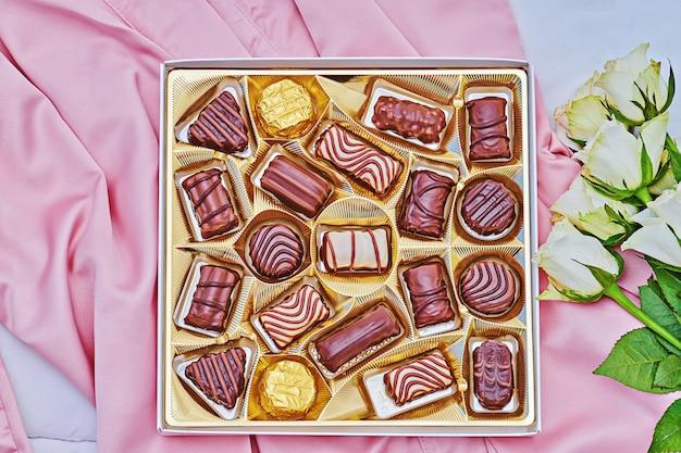 Caixa de presente dourada de chocolate sortido em seda rosa com buquê branco de rosa