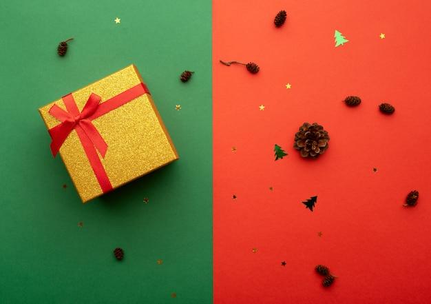 Caixa de presente dourada em um fundo brilhante com cones de estrelas e pequenas árvores de natal