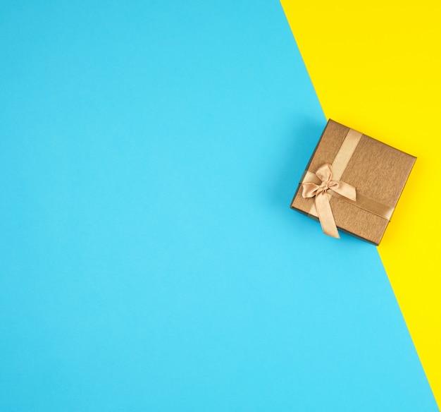 Caixa de presente dourada fechada com um arco