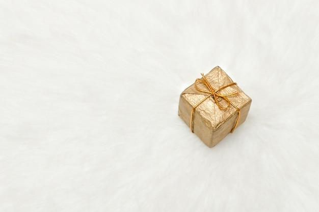 Caixa de presente dourada sobre fundo branco, copie o espaço. conceito de férias
