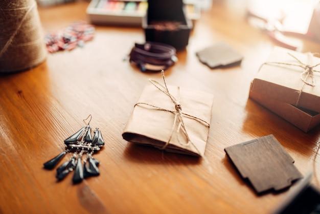 Caixa de presente e brincos artesanais na mesa de madeira, acessórios de bordado. joias artesanais, bijuteria