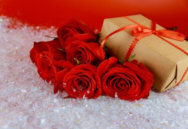 Caixa de presente e buquê de lindas rosas vermelhas na neve cintilante. conceito de dia das mães ou dia dos namorados.