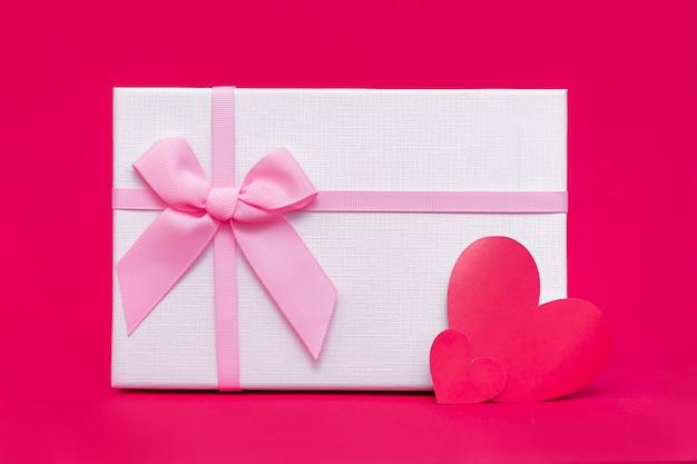 Caixa de presente e cartão em forma de coração na superfície rosa-vermelha