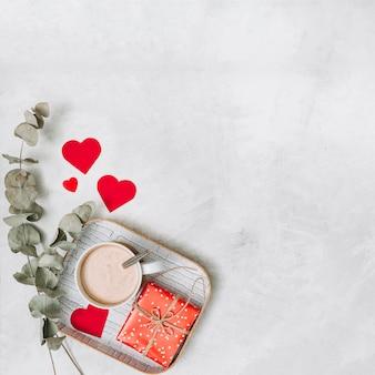 Caixa de presente e copo de bebida na bandeja perto de corações de ornamento e galhos de plantas