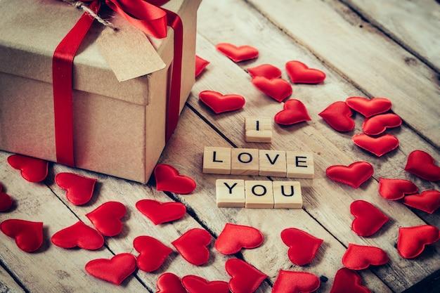 Caixa de presente e coração vermelho com texto de madeira para eu te amo no fundo da mesa de madeira.