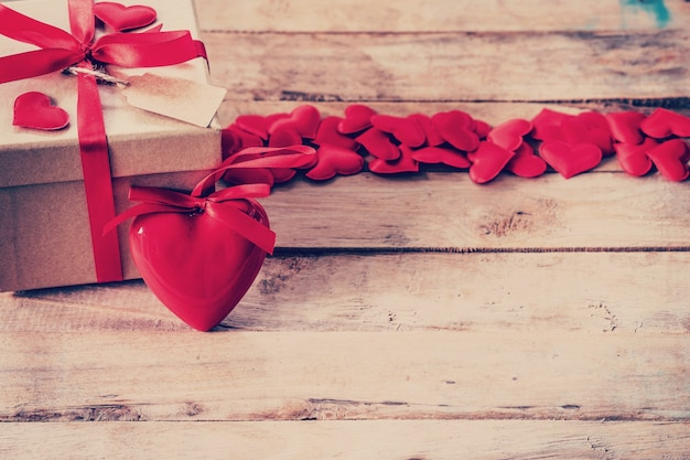 Caixa de presente e coração vermelho na mesa de madeira com espaço