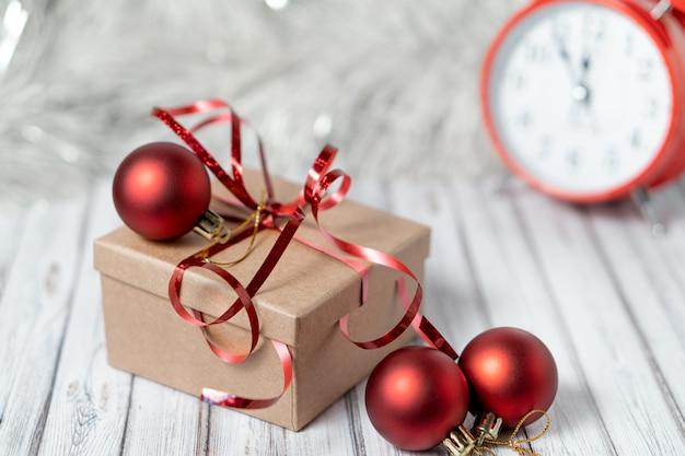 Caixa de presente e despertador turva em uma mesa de madeira decorada com uma guirlanda e bolas vermelhas de natal para o ano novo ou natal. copie o espaço