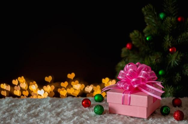 Caixa de presente e enfeites com árvore de natal e fundo de luzes de bokeh de forma de amor.