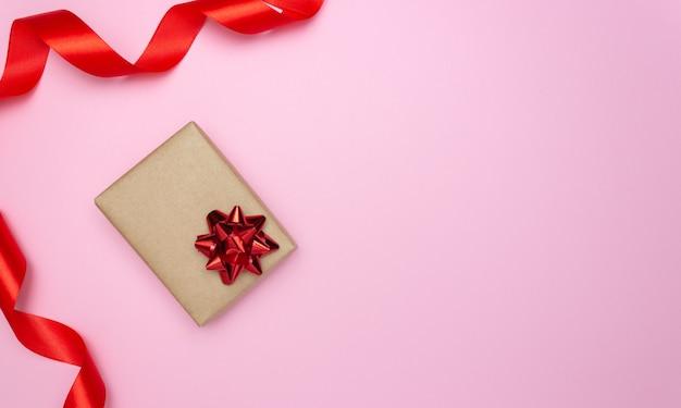 Caixa de presente e fita de cetim vermelha na lateral em um fundo rosa. espaço livre para texto. férias, natal, dia dos namorados.