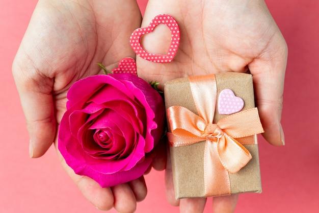 Caixa de presente e flor nas mãos. presente de dia dos namorados