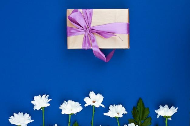 Caixa de presente e flores na mesa azul. cartão para aniversário, mulher ou dia das mães. vista do topo