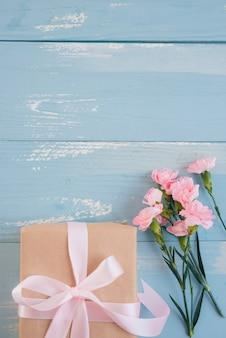 Caixa de presente e flores na vista superior do plano de fundo azul