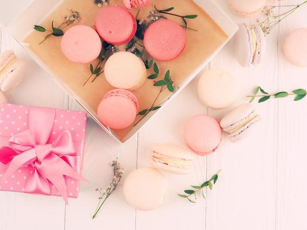 Caixa de presente e macarons na mesa branca