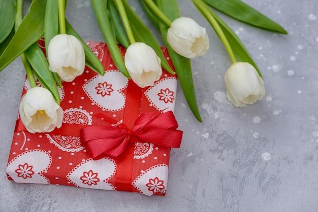 Caixa de presente e tulipas brancas. conceito de férias